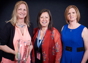 Christina Hamilton (from left), SanMar's account executive, and Susan Rye, SanMar's director of strategic accounts, receive the 2015 Supplier of the Year Award from Vicki Palm, The Vernon Company's director of marketing.